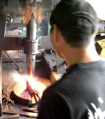 Forging the hagane, the cutting laminate of these knives, with a spring hammer.