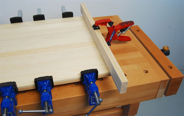 This clamp is being used to prevent bowing or cupping across the board during this glue up